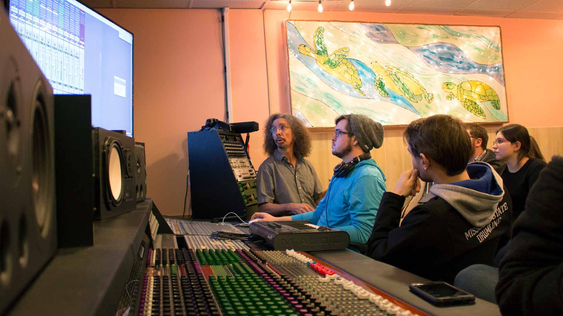 Professor helping students edit audio.